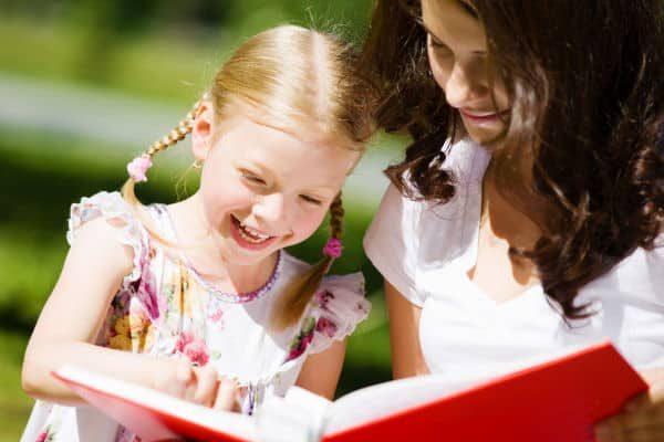 Mom and girl looking at scrapbook album